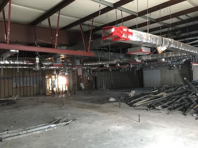 Photo of the new building during demolition. The ceiling has been ripped out and duct work is exposed.